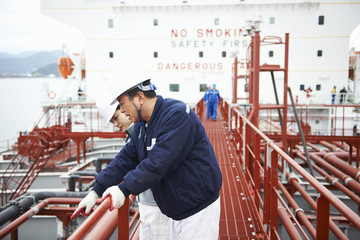 Two workers having discussion at shipping port, GoSeong-gun, South Korea