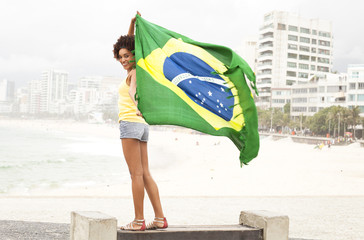 Portrait of young woman holding up Brazilian flag on park bench, Ipanema beach, Rio De Janeiro, Brazil