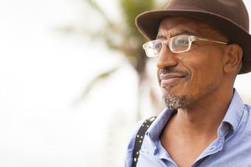 Portrait of mature man wearing trilby at Ipanema beach, Rio De Janeiro, Brazil
