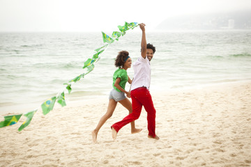 Couple playing with string of flags on beach, Rio de Janeiro, Brazil