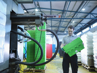 Worker inspecting plastic crates in plastics factory