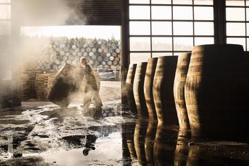 Worker pushing barrel in warehouse