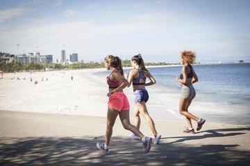 Three young women jogging on beach, Rio De Janeiro, Brazil