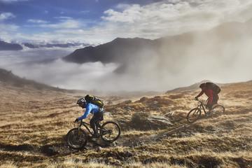 Two men mountain biking in landscape