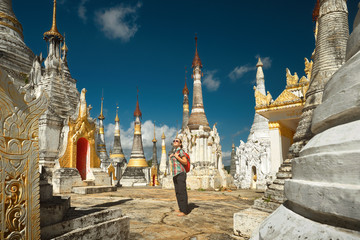 Woman traveling with backpack and looks at stupas Buddhist temple