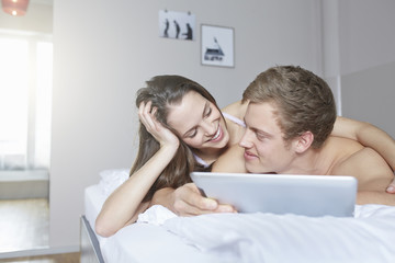 Young couple browsing digital tablet on bed