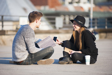Young couple sitting cross legged using smartphone