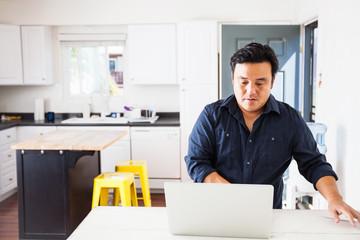 Mature man typing on laptop at kitchen table