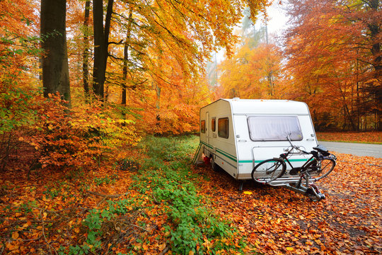 Caravan trailer with a bicycle and a car parked in a golden beech tree forest. Colorful red, orange and yellow leaves on the ground. Autumn landscape. Leisure activity in Heidelberg, Germany