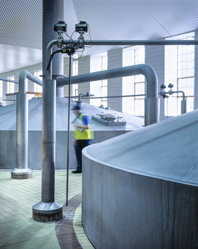 Worker in brewing hall of commercial brewery