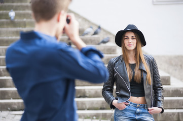 Young man photographing young woman