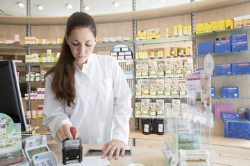 Pharmacist in pharmacy stamping prescription