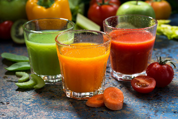 assortment of fresh vegetable juices on a blue background