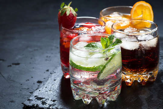 assortment of iced fruit drinks on a dark background