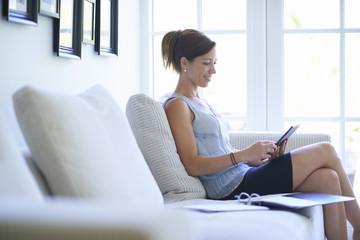 Mid adult woman using digital tablet on living room sofa
