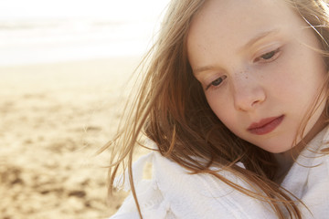 Close up portrait of girl wrapped in blanket on beach