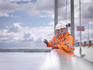 Bridge workers on parapet of suspension bridge. The Humber Bridge, UK was built in 1981 and at the time was the world's largest single-span suspension bridge