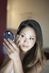 Attractive woman using compact mirror to check make-up