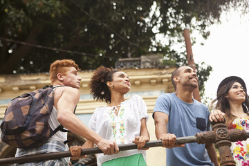 Small group of friends holding onto railing, smiling, low angle view