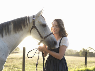 Portrait of teenage girl and her grey horse in sunlit field