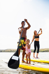 Portrait of couple and toddler daughter standup paddleboarding, Carlsbad, California, USA