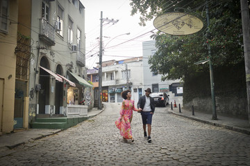 Couple walking down cobbled street, hand in hand