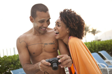 Couple laughing at photographs on digital camera at hotel poolside, Rio De Janeiro, Brazil