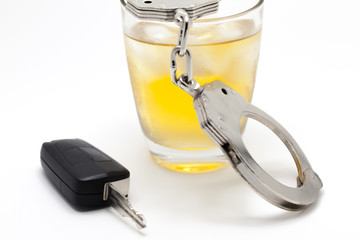 Car key with glass of whiskey and handcuffs - drive under influence concept