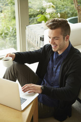 Portrait of smiling man sitting on floor at home looking at laptop and drinking cup of coffee