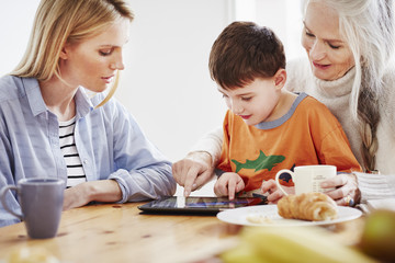 Three generation family using digital tablet