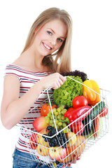 Isolated young woman holding basket of vegetables on light backg