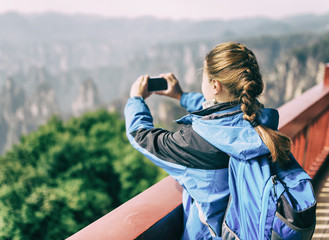 Female tourist taking photo of mountains. Toned image