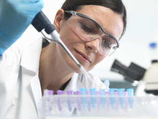 Scientist pipetting DNA sample into vial in lab