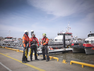 Offshore windfarm engineers on quayside with boats in the background