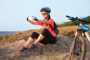 Adult attractive female cyclist sits on the rock and makes the p
