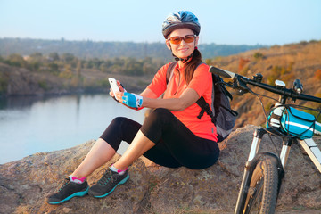 Adult attractive female cyclist smiling.