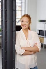lächelnde junge frau steht mit verschränkten armen im büro