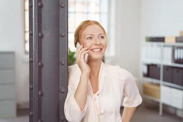 moderne junge frau im büro telefoniert mit ihrem handy