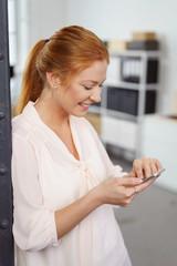 frau steht im büro und tippt eine nachricht auf ihrem smartphone