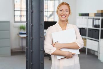lächelnde junge geschäftsfrau mit unterlagen im büro