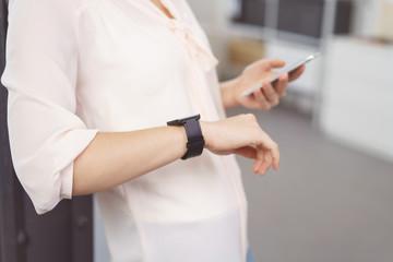 frau mit smartwatch und handy