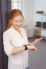 frau schaut lächelnd auf ihre smartwatch