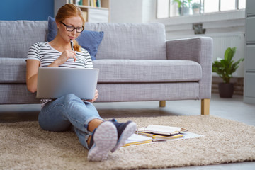 studentin lernt zu hause mit laptop und unterlagen
