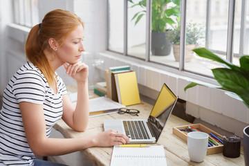nachdenkliche studentin sitzt zuhause am tisch und schaut auf laptop