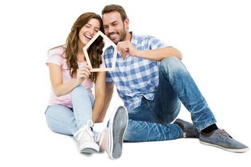 Young couple holding house shaped popsicle sticks