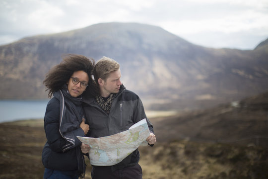 Mid adult couple in mountains with map