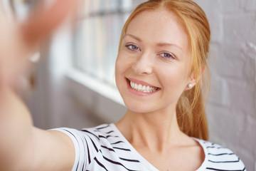 lachende junge frau macht ein selfie