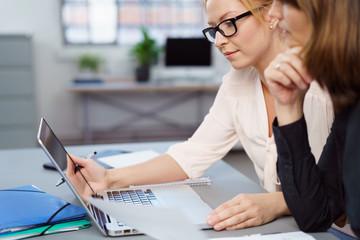 zwei kolleginnen arbeiten zusammen am laptop