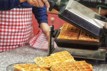 Woman preparing fresh Waffle for dessert