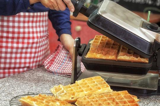 Woman preparing fresh Waffle for dessert